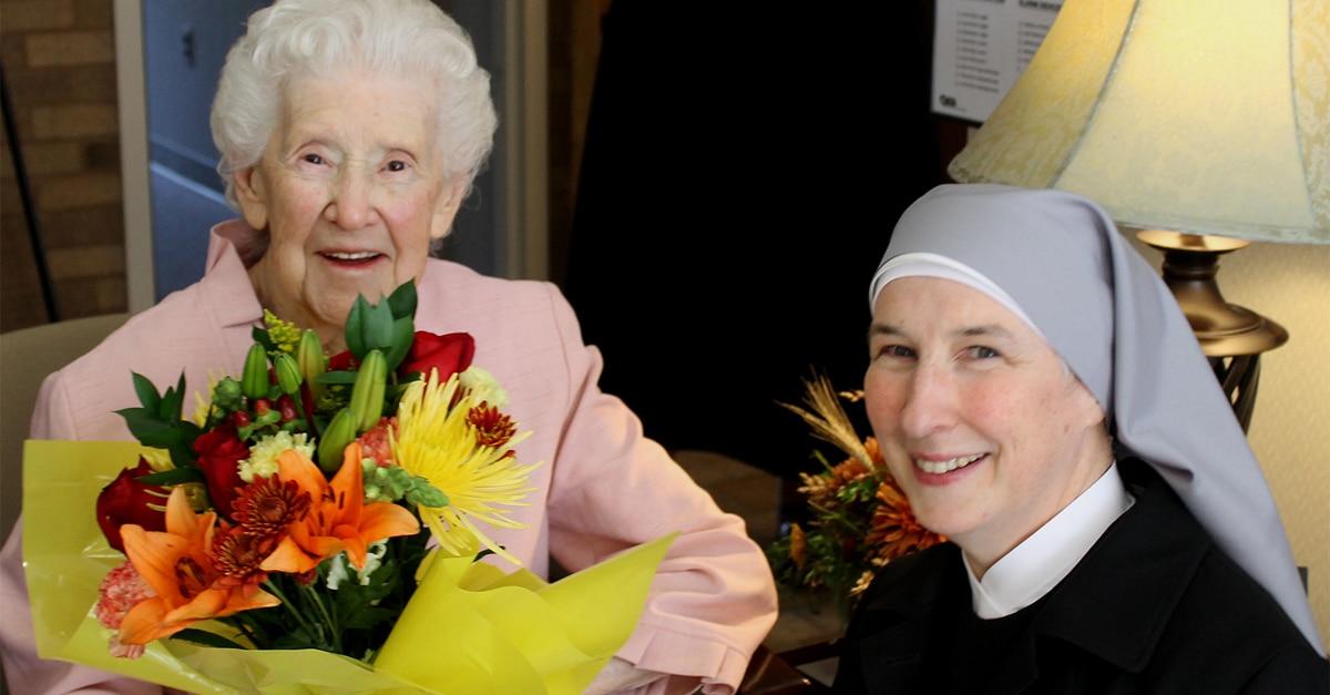 petite soeur offrant un bouquet de fleur à une personne âgée