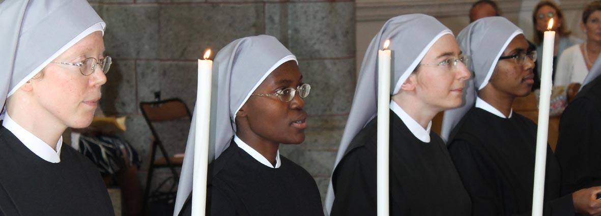 visages de Petites soeurs avec cierges lors de leurs voeux perpétuels